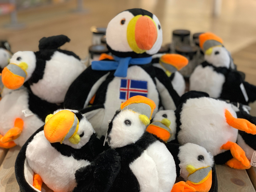 Pile of soft toy puffins one with the Iceland flag. The best Iceland souvenirs to take home.