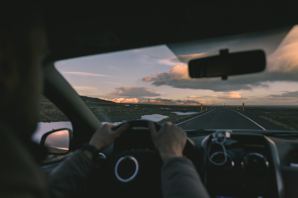 View out of windscreen with a man driving safely in Iceland at dusk.