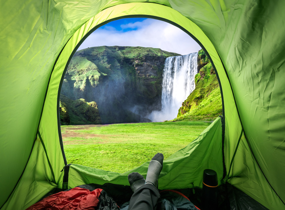 View from inside a green tent to a waterfall in the distance. Iceland camping law.