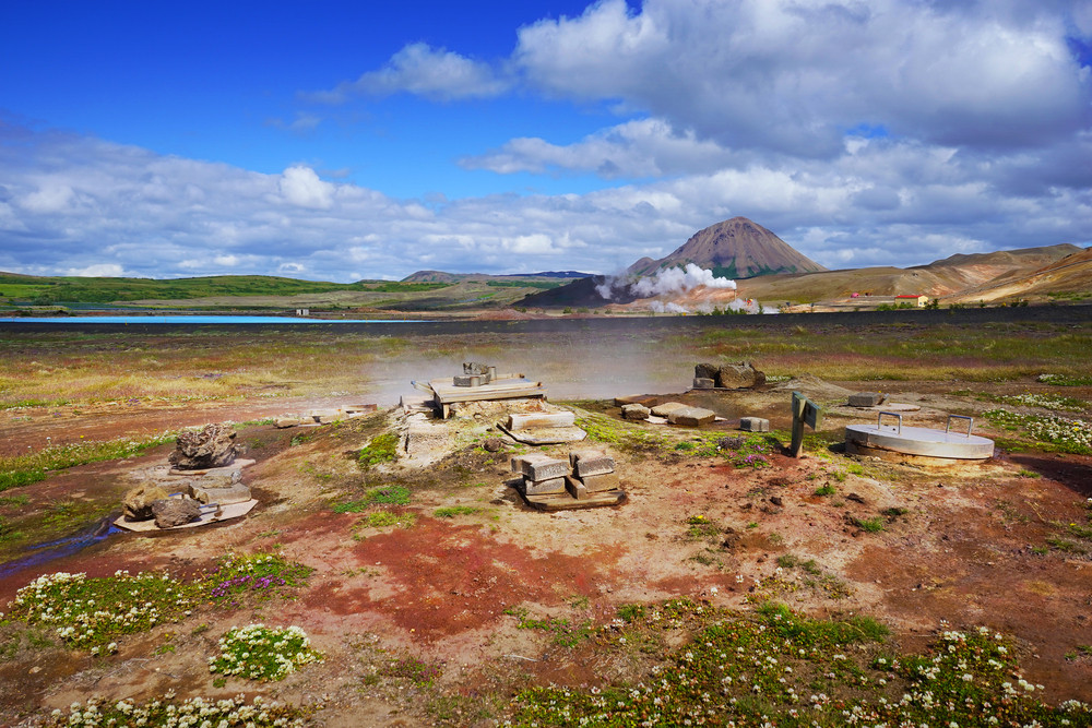 Wooden boxes on red earth with steaming hot springs nearby. A traditional way to bake rye bread. What food should I try in Iceland?
