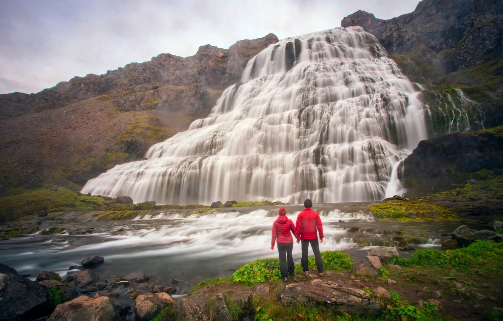 Couple in warm jackets hold hands and look out across a beautiful waterfall. Iceland honeymoon ideas.