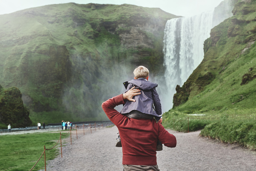 Child on a man's shoulders walking towards a huge and impressive waterfall. Family travel in Iceland.
