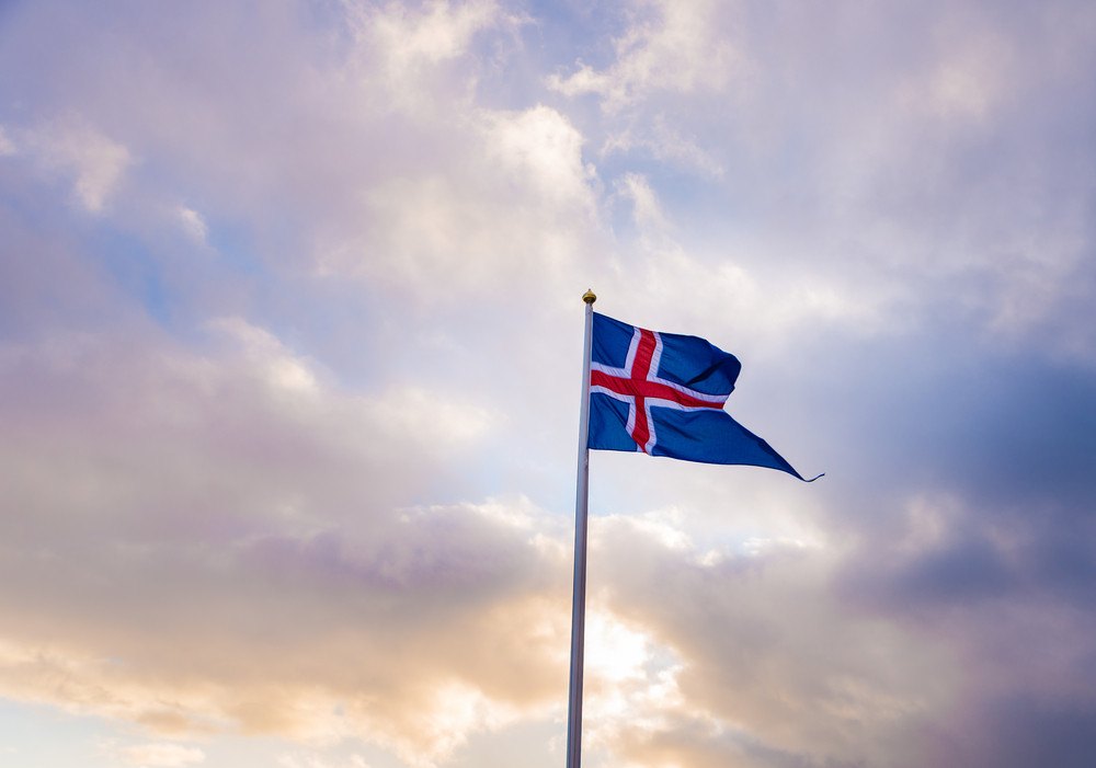 Iceland national flag on blue and cloudy sky