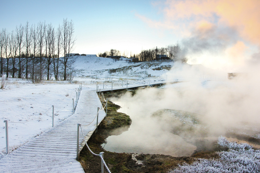 Steamy pool in a snowy setting. Cool winter light and a wooden walkway in snow. Hot springs in Iceland.