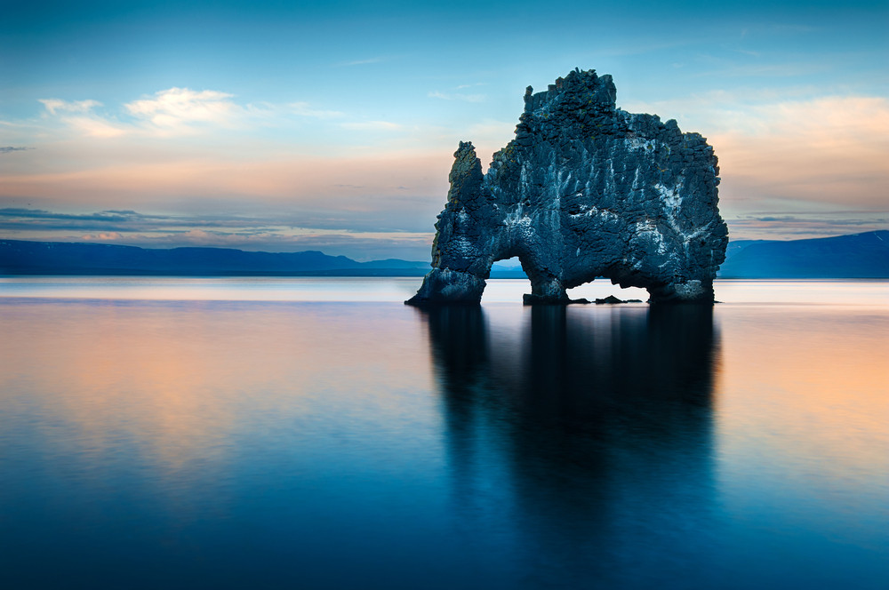 Hulking black rock with undercuts on the beach with pink and blue sky. Photography locations in Iceland.