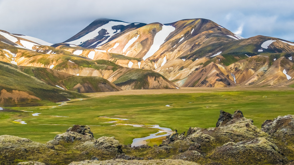 Colourful mountains orange, umber and snow. A green meadow with waterways. Hot springs in Iceland.