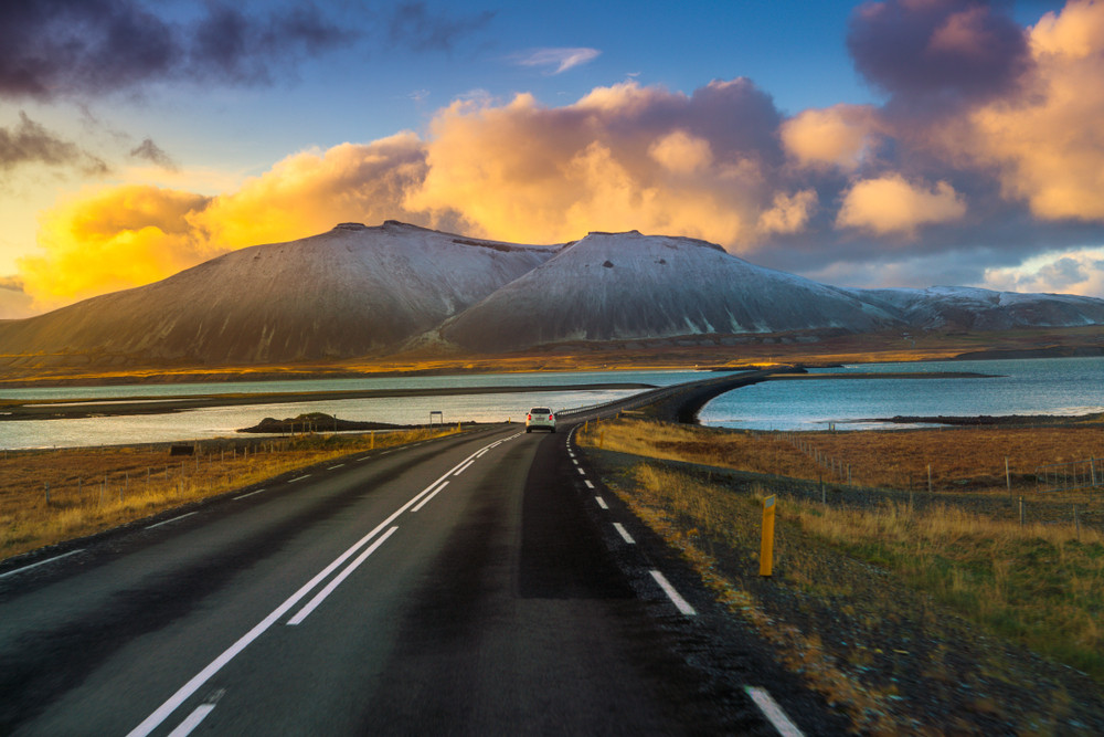 Two-lane road heading off into beautiful countryside of lake and mountains under a sunset sky. Colours of blue, orange and gold driving the Iceland ring road