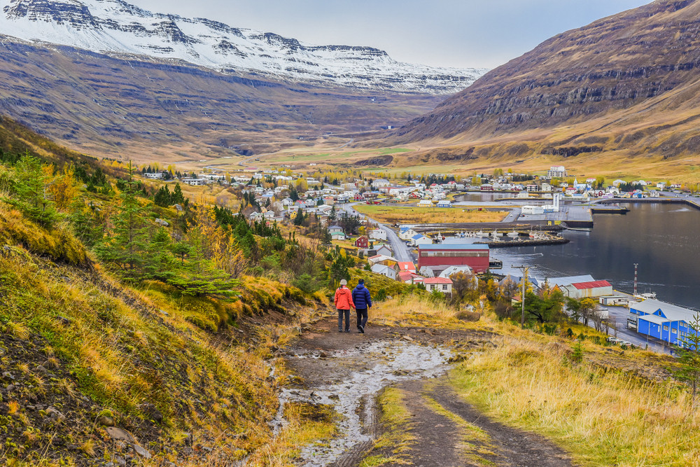 Couple hiking near fjord and town in autumn landscape. Iceland in Fall.
