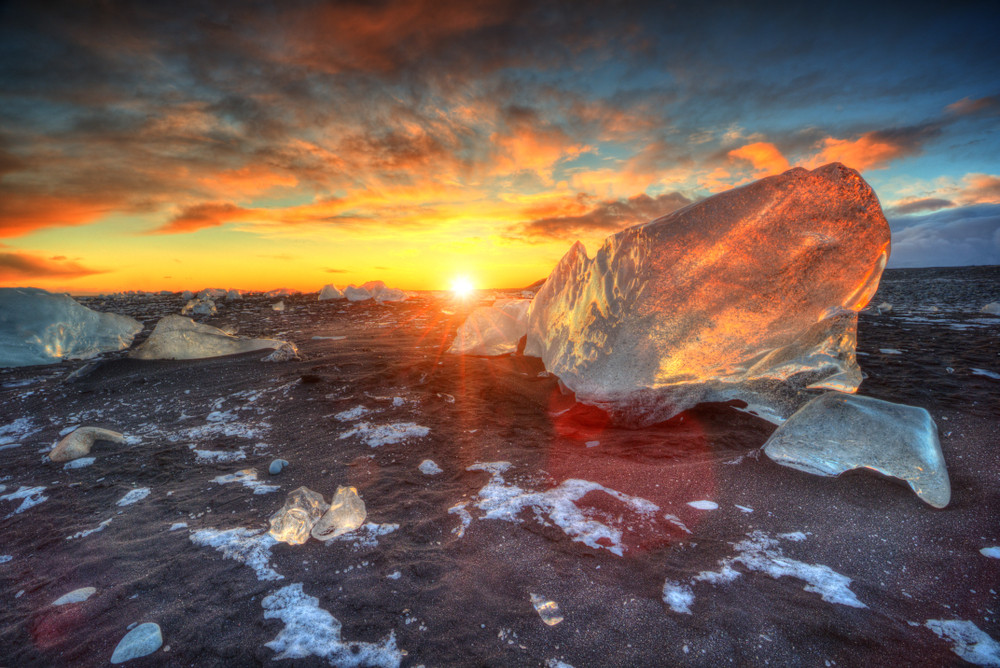 Sunset over a stretch of sand dotted with ice. Photography locations in Iceland.