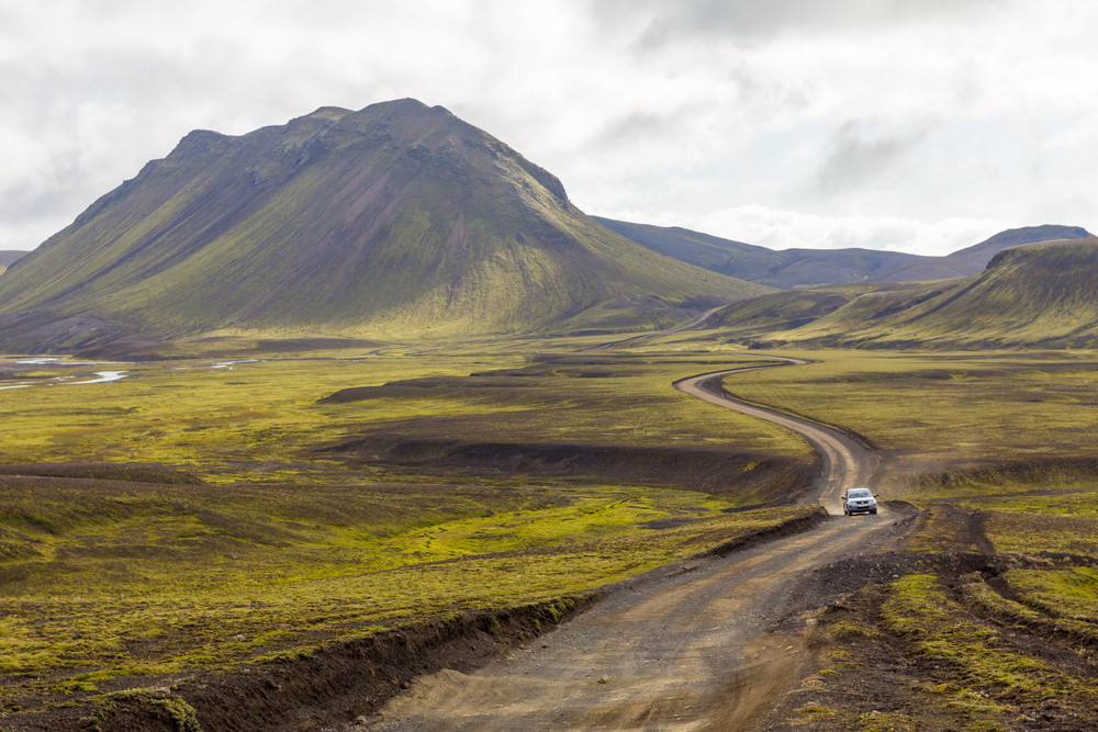Car in the distance on a remote travel road. starkly beautiful hilly scenery on this self drive road trips in Iceland.