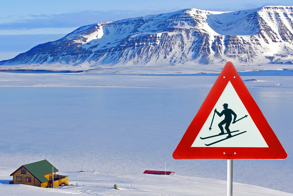 Skiing in Iceland sign post with background of calm winter scene.