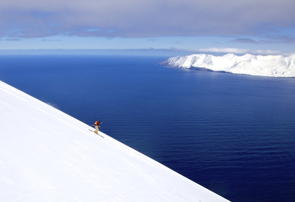 Ski slope with a backdrop of the wide blue ocean. One skier glides down. Skiing in Iceland.