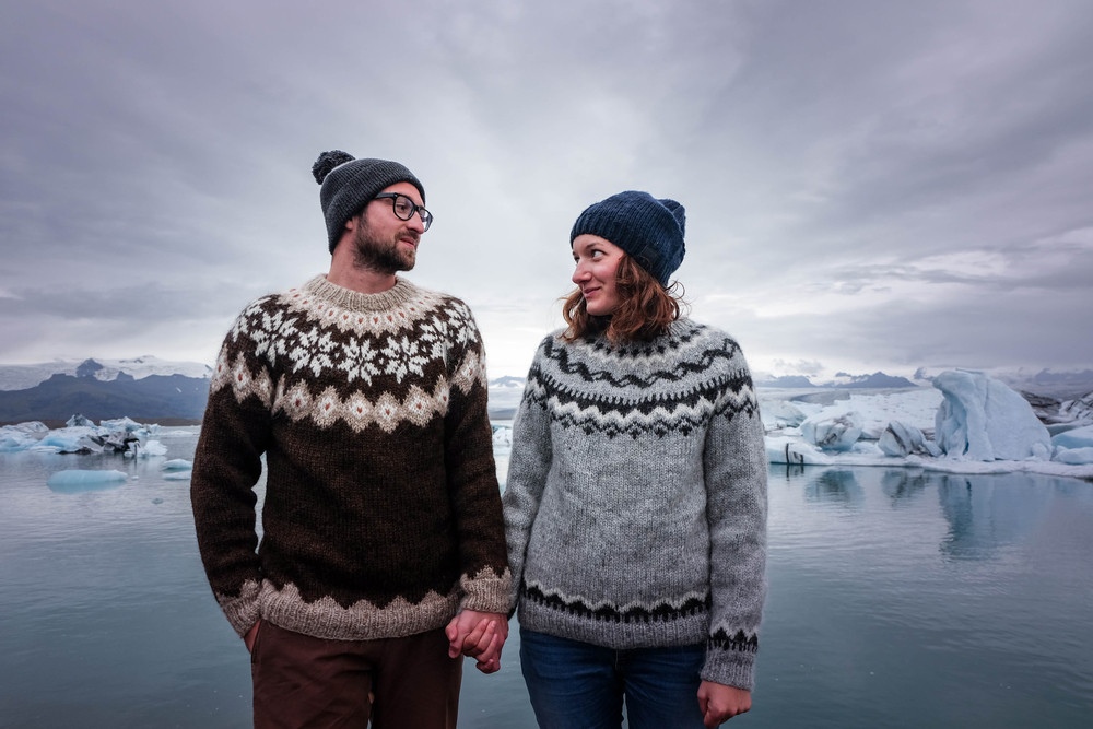 Couple wearing traditional icelandic knitted sweaters with an icy lake scene behind. The best Iceland souvenirs.