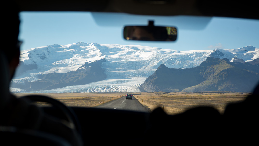 View out of a driving car at a glacier and mountain in the distance. Drive safely in Iceland.