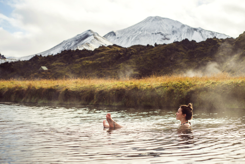Girl floating in a natural pool snow capped mountains in the distance and steam rising from water. Hot springs in Iceland.