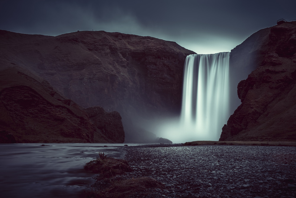 Dark arty image of white waterfall surrounded by black rock. Photography locations in Iceland.