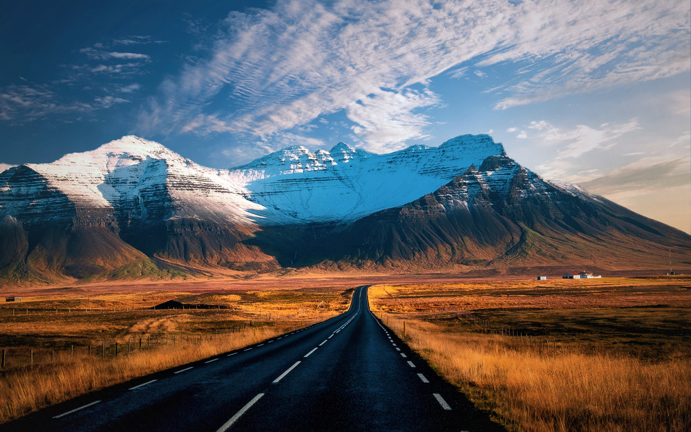 An empty road stretches out into a beautiful mountain scene.  Sticking to the Iceland speed limit can be hard on the open road.