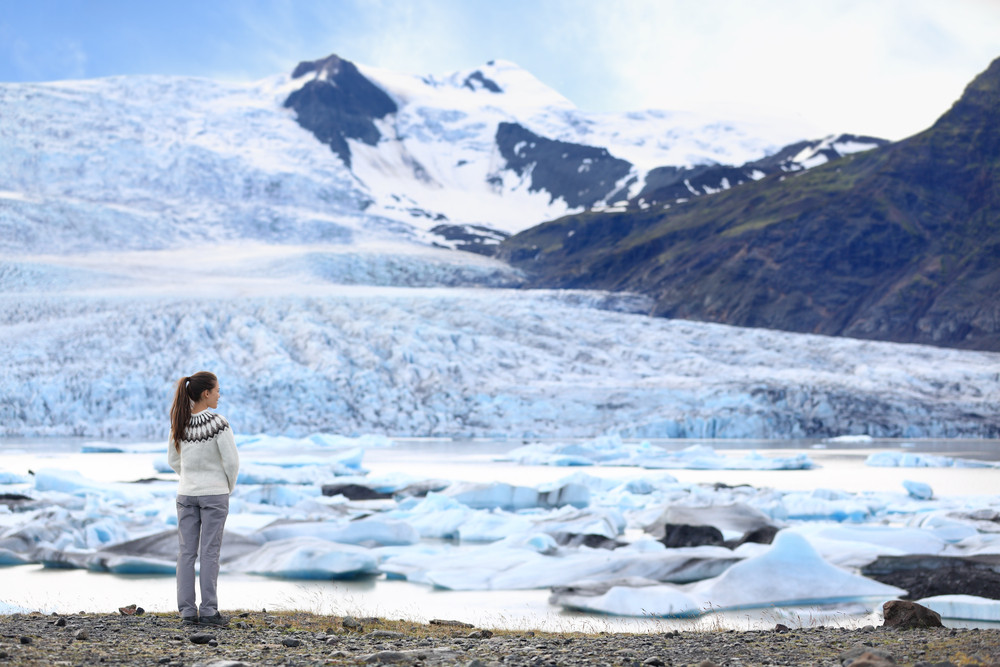 Young woman stands looking out across a glacier. Solo travel in Iceland.