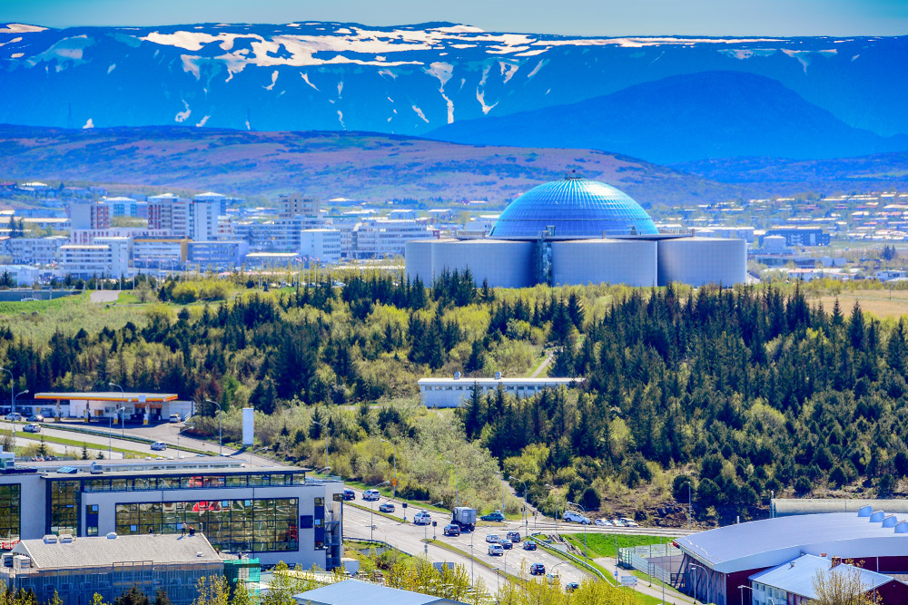 Cityscape of Reykjavik under blue skies. An impressive dome building with silos dominates the view with snowy mountains in the background. The Perlan building is home to one of the most modern museums in Iceland.