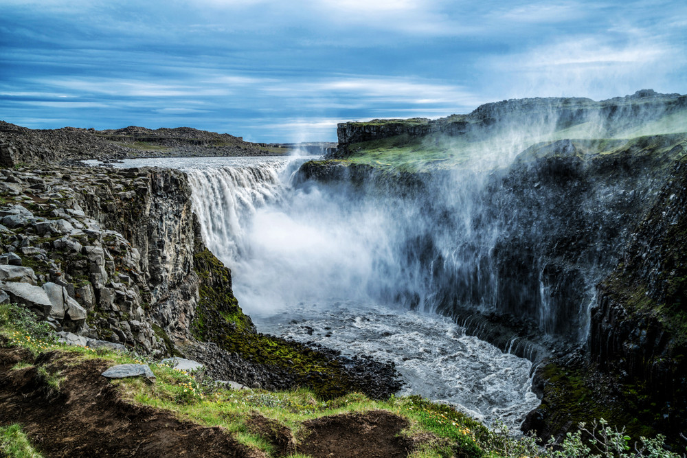 Large and powerful waterfall from a distance. Rocky terrain and water mist. Iceland's Diamond Circle