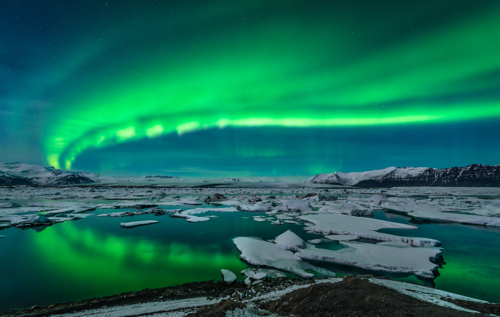 Bright green Northern Lights over a lake with broken ice. Seeing the Aurora is possible in early spring in Iceland.
