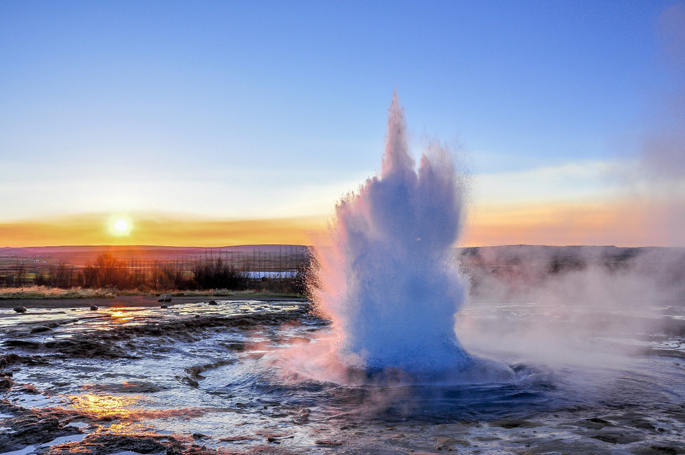 A spurting active geyser at sunrise. Camping Golden Circle route Iceland.
