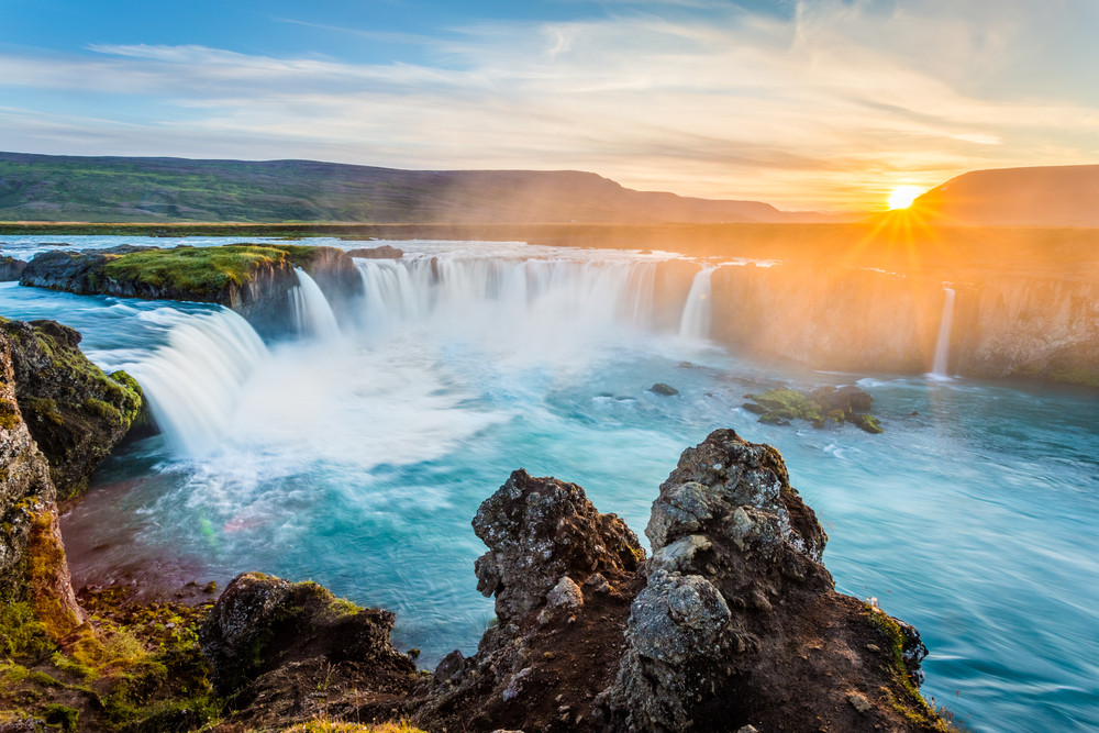 Low sun over a wide horseshoe waterfall. How to save money in Iceland.