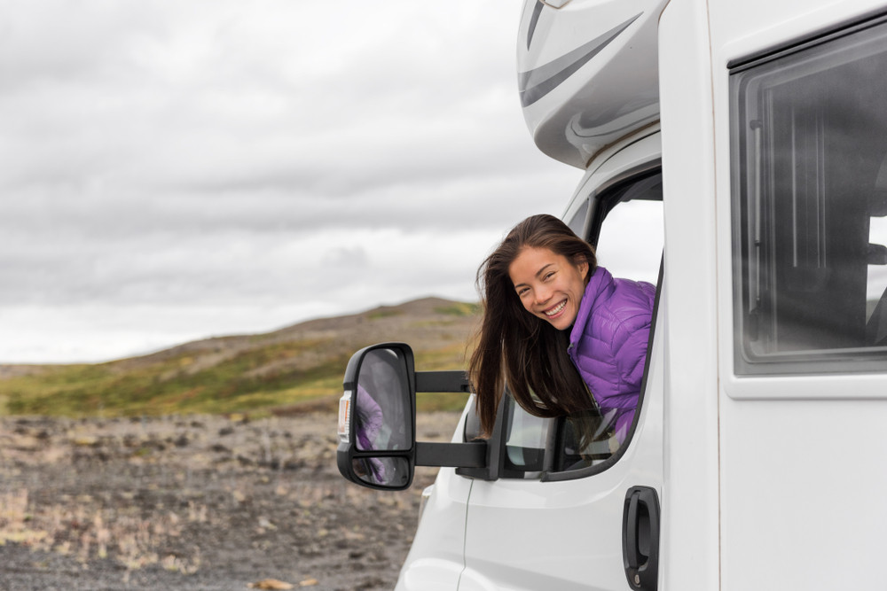Smiling woman with long dark hair leaning out of a motorhome window. How expensive is Iceland?