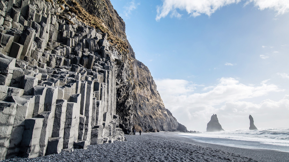 Basalt columns, black sand and sea stacks with blue skies on Vik's volcanic black sand beaches.