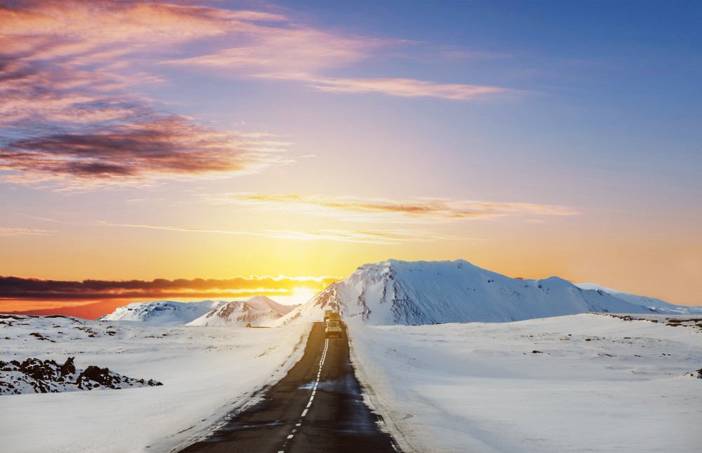 Winter road at sunset leading into snowy hills. Camping and caravanning in Iceland in winter.