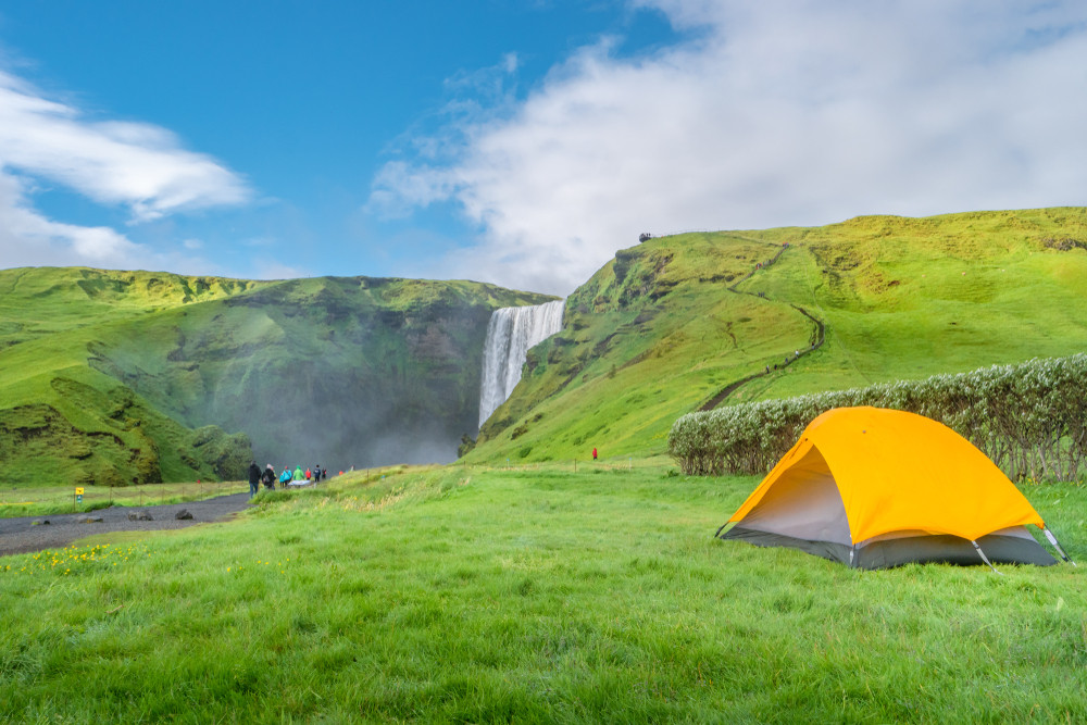 Bright yellow tent on lush green field with waterfall in distance. Right to roam in Iceland.