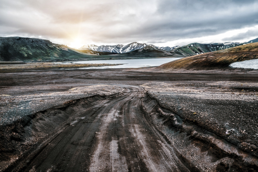 Beautiful mountain road with mountains and subdued colours. The highlands are one of the most spectacular road trips in Iceland.