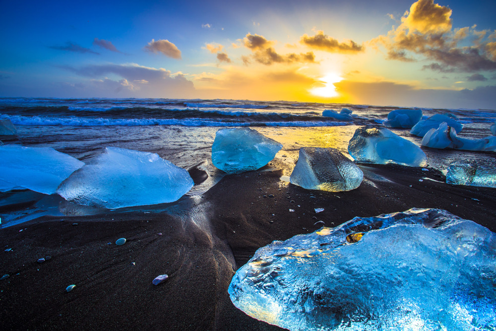 A black sand beach at sunset dotted with glowing blue ice blocks. The sea rolls in behind them. Diamond Beach is one of the highlights of South Iceland