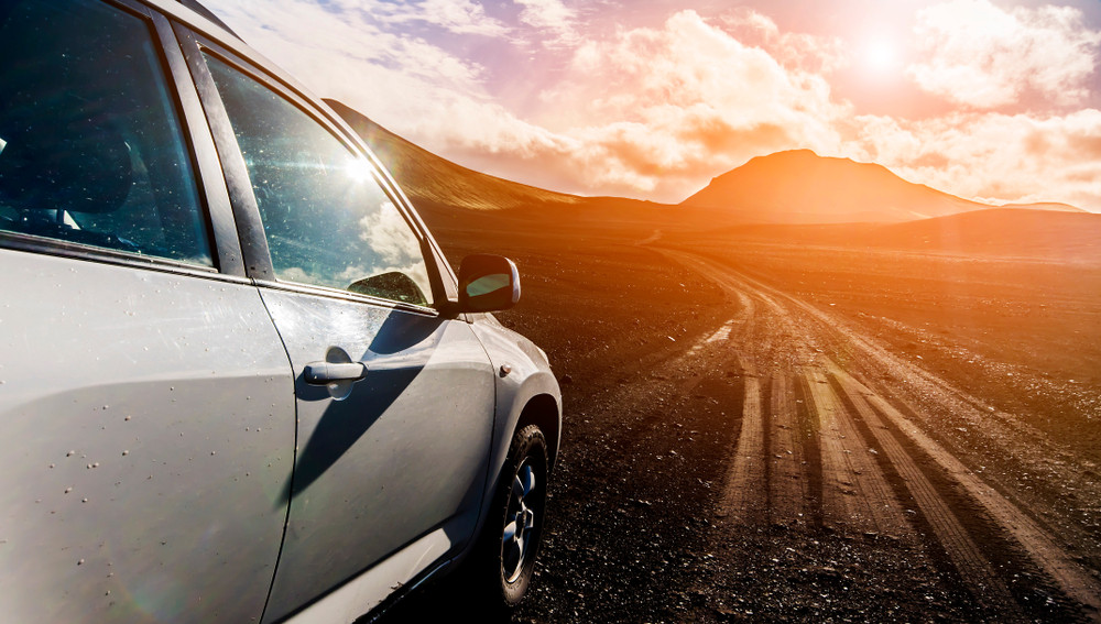 Bright sunset and a car driving down gravel roads in Iceland.