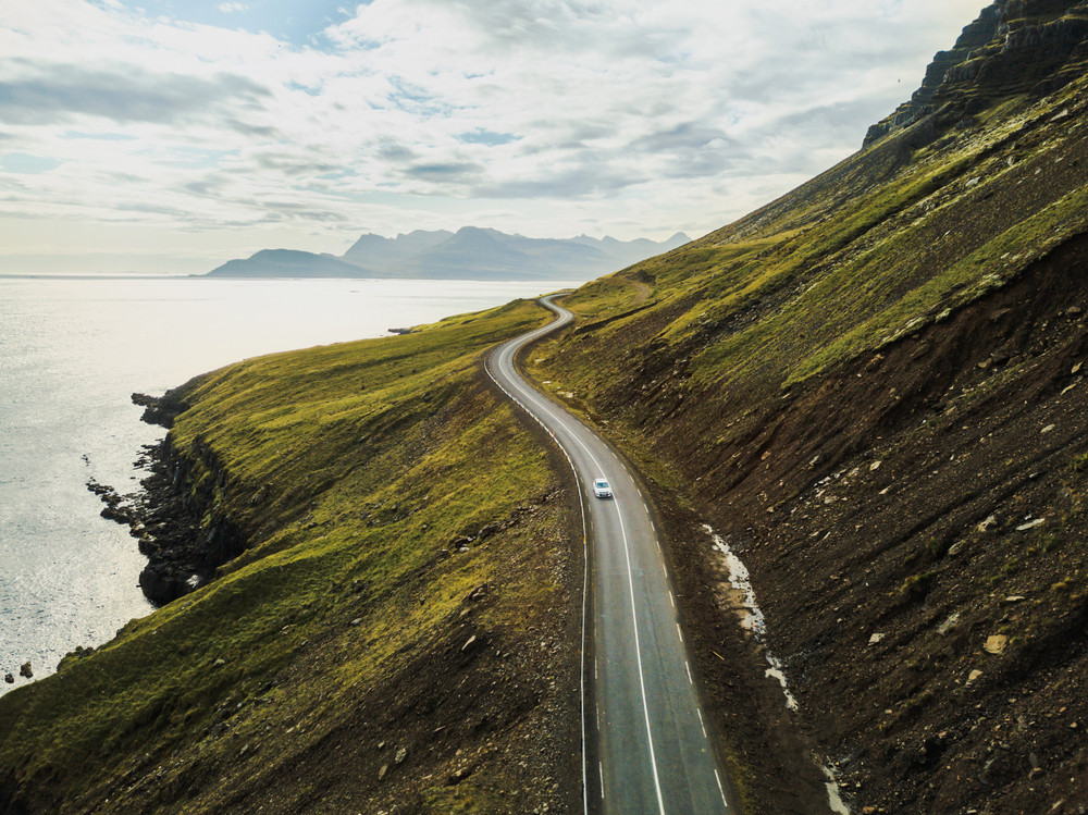 A dramatic road winds around a headland between the ocean and a steep grassy slope. Iceland speed limit.