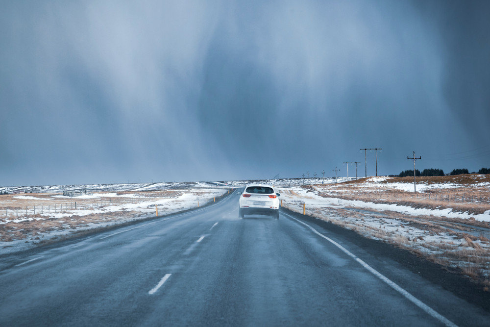 A car drives through bad weather on the road in Iceland. Just how windy is Iceland?