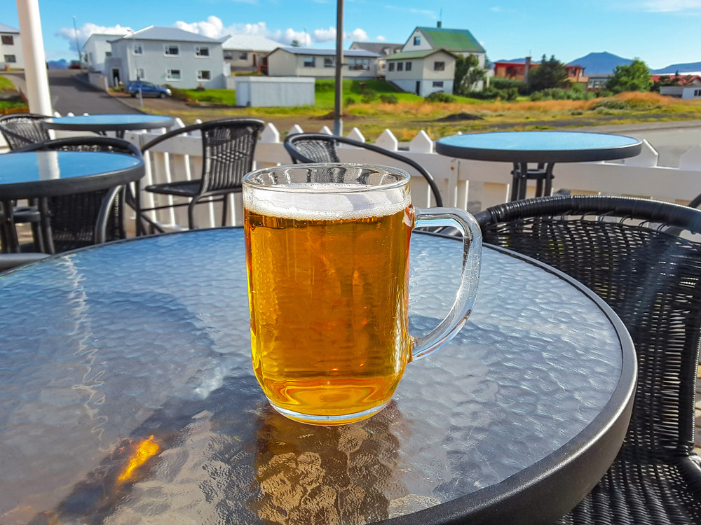 Mug of Icelandic beer on an outside bar table in the sun.