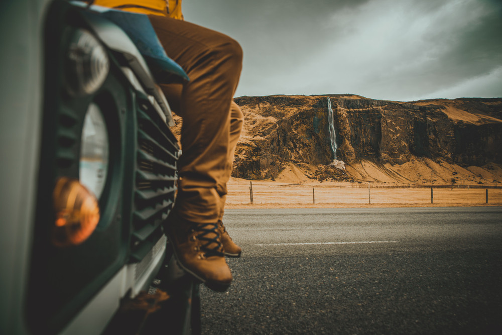 Person in walking boots sitting on hood of jeep with waterfall in background. Do i need a 4 x 4 in Iceland?