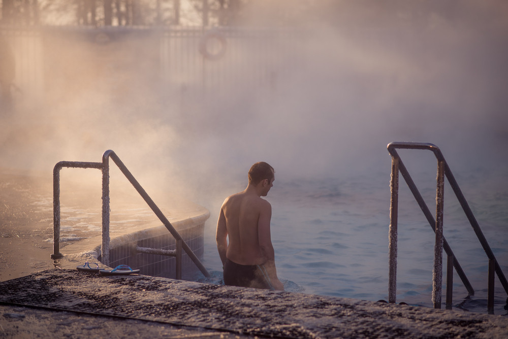 Man stepping into steamy pool of a hot spring. A good way to unwind during Iceland Airwaves Festival.