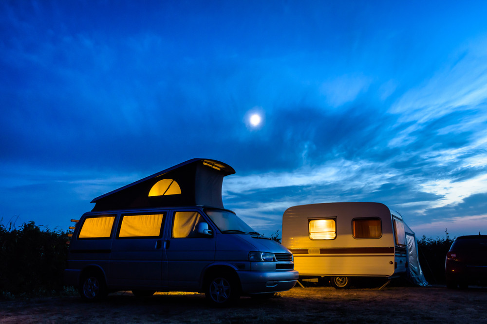 Camper and caravan with glowing lights and night sky. Camping and caravanning in Iceland in winter.