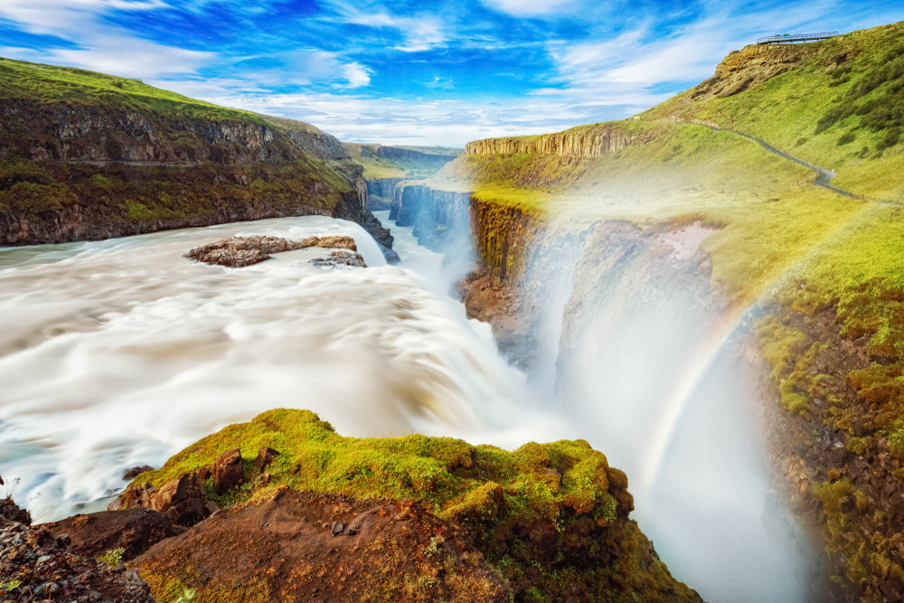 wide view of Gullfoss waterfalls in Iceland with rainbows arcing across the gorge and white water.