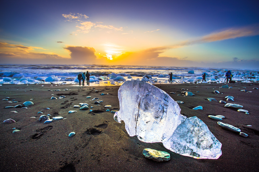 Pieces of ice dot a dark sand beach, people at the shoreline and sunset sky. Diamond Beach is one of Iceland's South Coast highlights