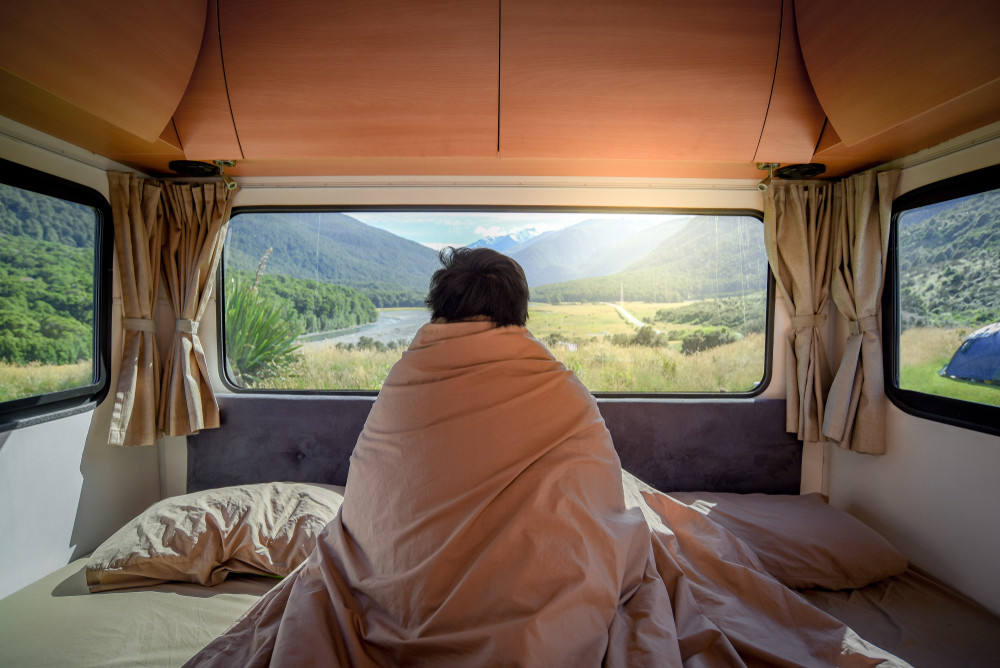 Person wrapped in duvet looking out at beautiful landscape from motorhome bed in Iceland.