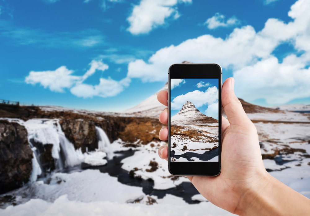 View of waterfalls and snowy mountain with a phone held up in front. Best travel apps tourists in Iceland