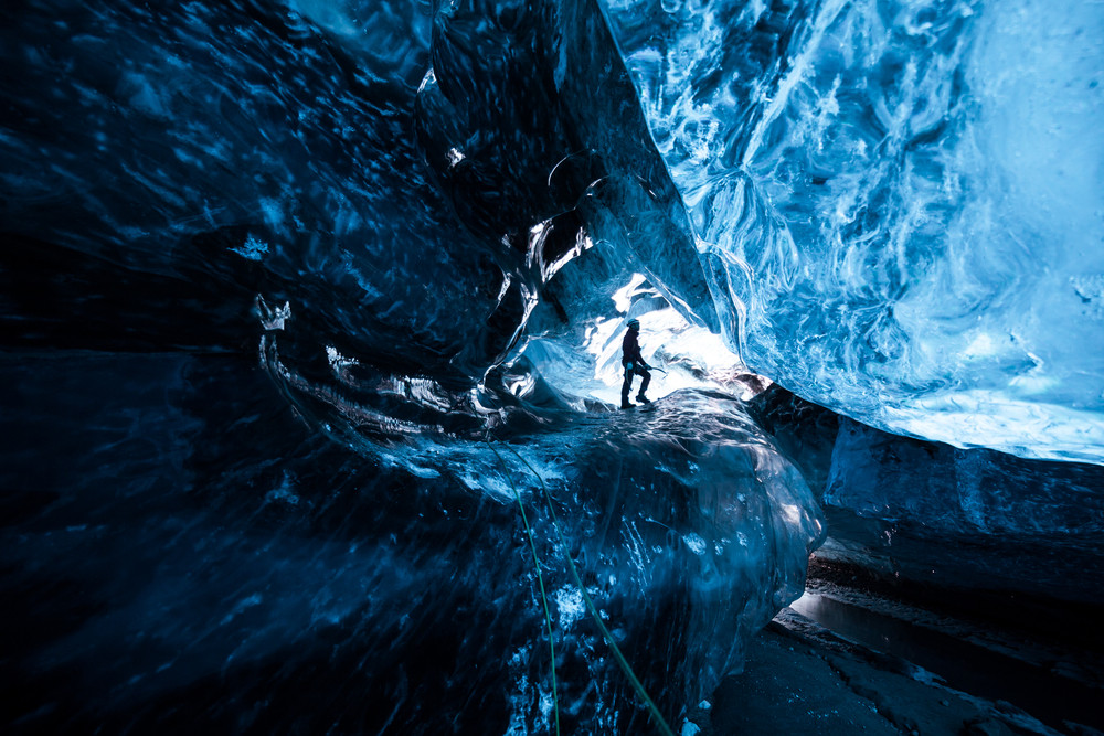 Person standing inside a blue ice cave at Jokulsarlon Glacier Lagoon Iceland.