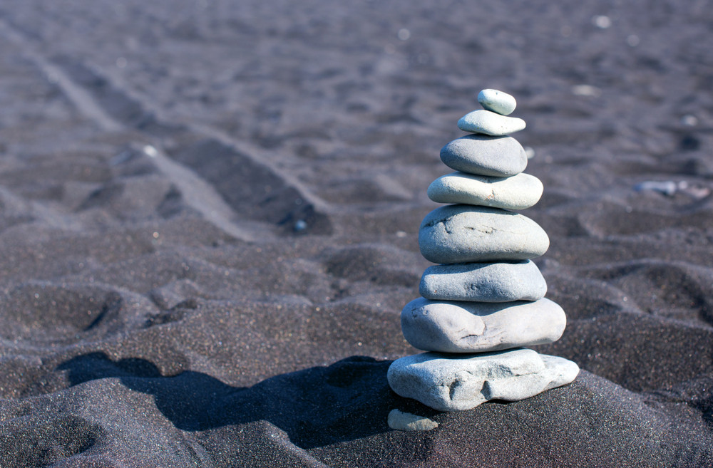 Building cairns in Iceland. White pebble stack on black sand beach.