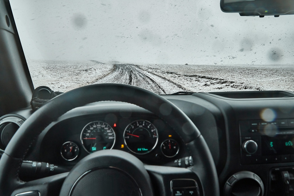 View from a vehicle driving seat over steering wheel onto a snowy gravel road beyond. Car insurance in Iceland.