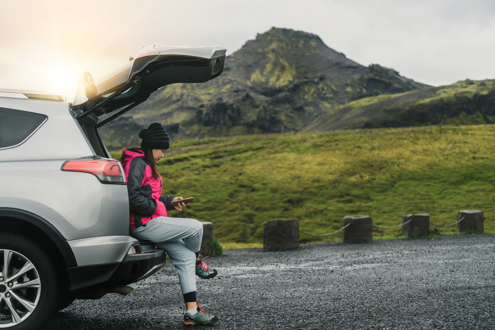 Woman in winter gear looking at phone perched on back of a car in the countryside. Useful travel apps for tourists in Iceland.