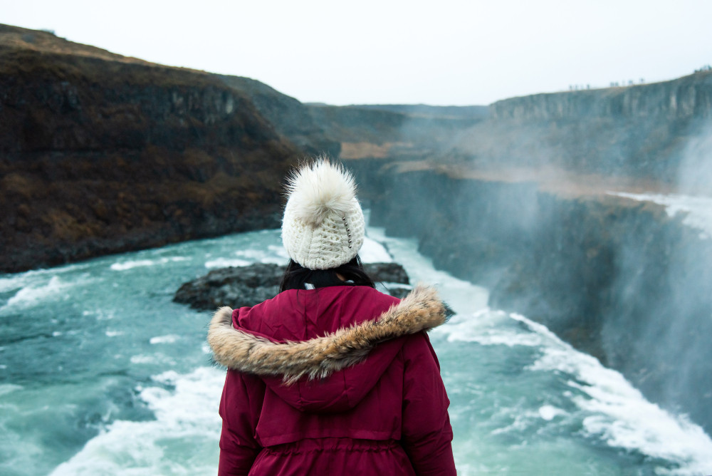 Woman in winter wear stands in front of Gullfoss Waterfall. Camping Golden Circle, Iceland.