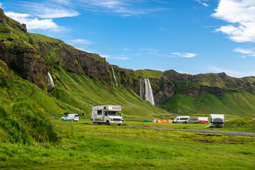 Campervans parked up near a beautiful waterfall surrounded by green meadows and banks. Iceland in June is a good time to camp.